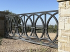 "Entry Gate / 'Rings' Design / Welded Steel / 14' x 44"" / Tesuque, NM / Sendero del Luz"